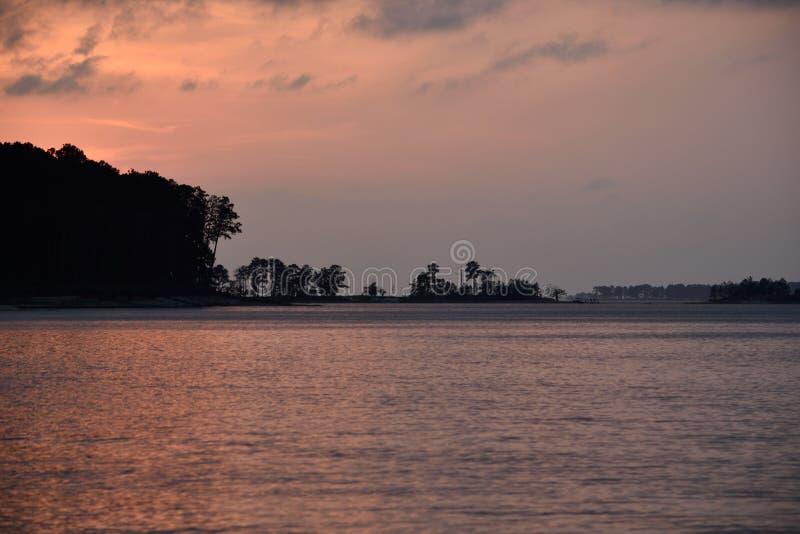 Rose d'or de coucher du soleil sur le lac dans les couleurs semblables photo stock