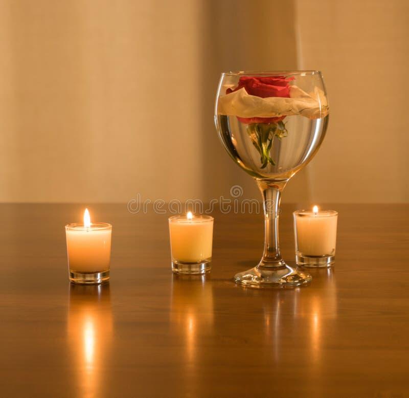 Rose dans un verre et des bougies photo libre de droits