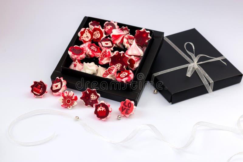 Rose de meringue avec les fleurs rouges dans la boîte noire  image stock