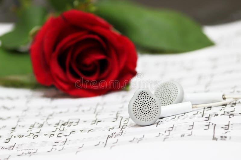 Rose de rouge, écouteurs, musique de feuille de piano photos stock
