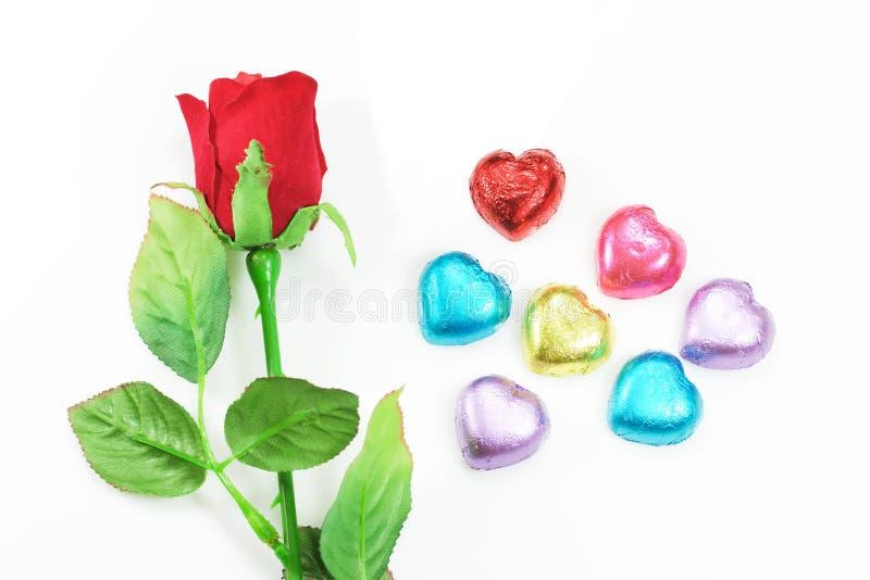 Rose de rouge et décoration colorée de coeur pour le jour de la valentine sur le fond blanc photo libre de droits