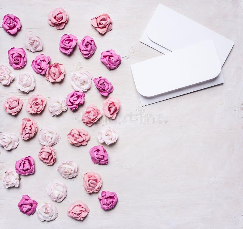 Rose di carta variopinte con le buste, confine di San Valentino, con la fine rustica di legno bianca di vista superiore del fondo fotografia stock libera da diritti