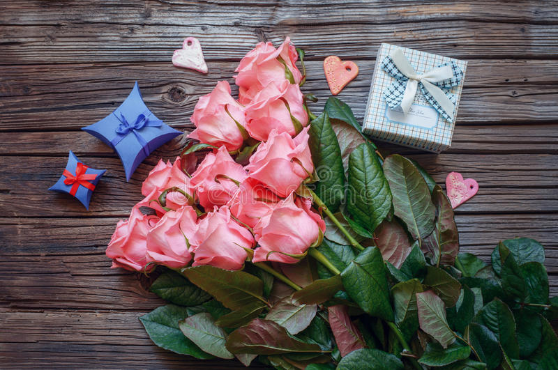 Rose e contenitore di regalo sopra vecchio fondo di legno fotografie stock libere da diritti