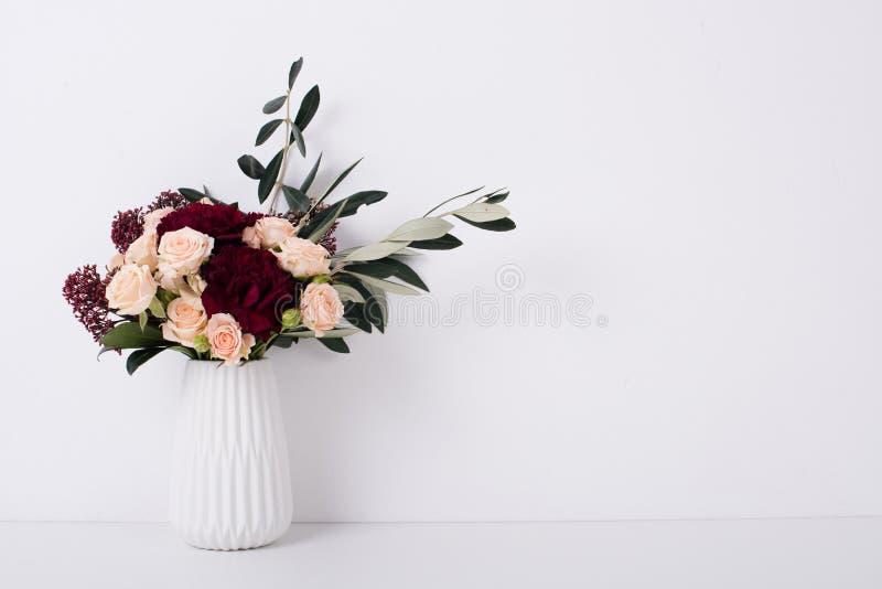 Rose e garofani in un vaso nell'interno bianco fotografie stock