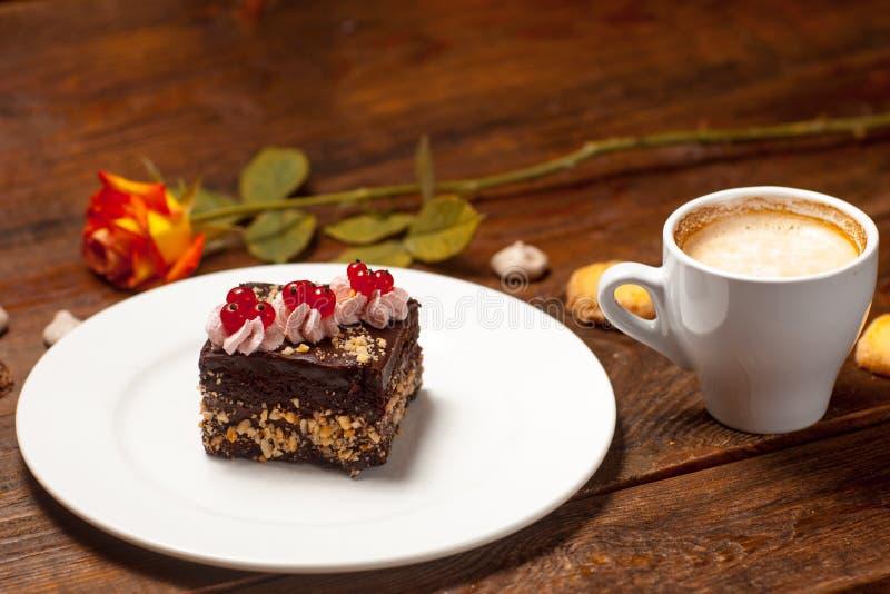 Rose, eine Schale des Cappuccinos und des Kuchens lizenzfreie stockbilder
