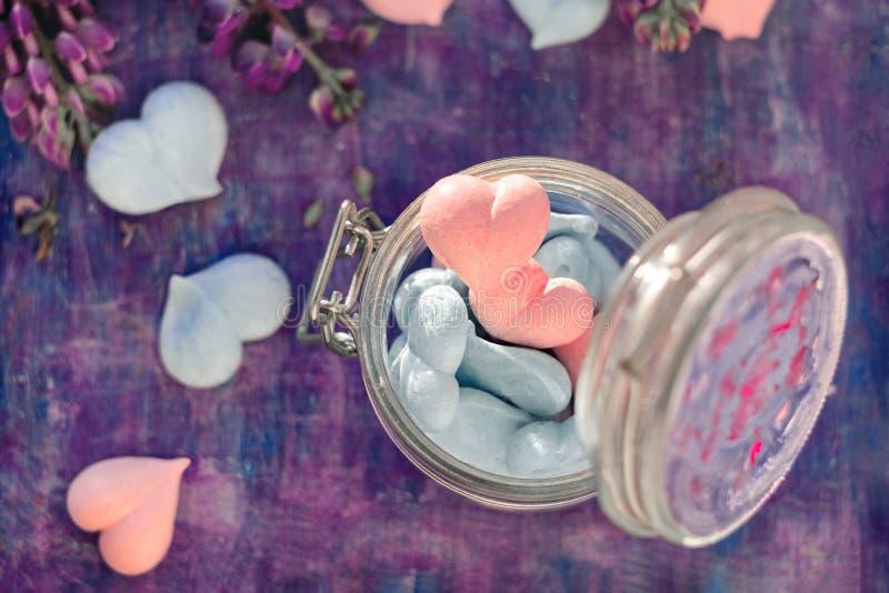 Rose et coeurs bleus de meringue dans le pot en verre sur le fond pourpre peint avec les fleurs de loup images libres de droits