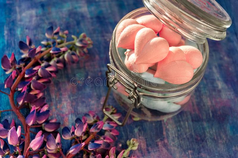 Rose et coeurs bleus de meringue dans le pot en verre sur le fond pourpre peint avec les fleurs de loup photographie stock libre de droits