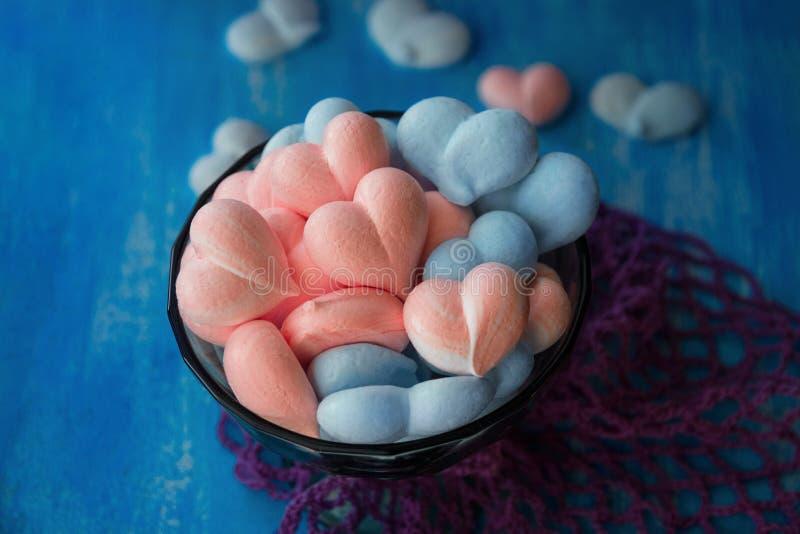 Rose et coeurs bleus de meringue sur le fond bleu peint avec la rayure et la maille violette de coton photos stock