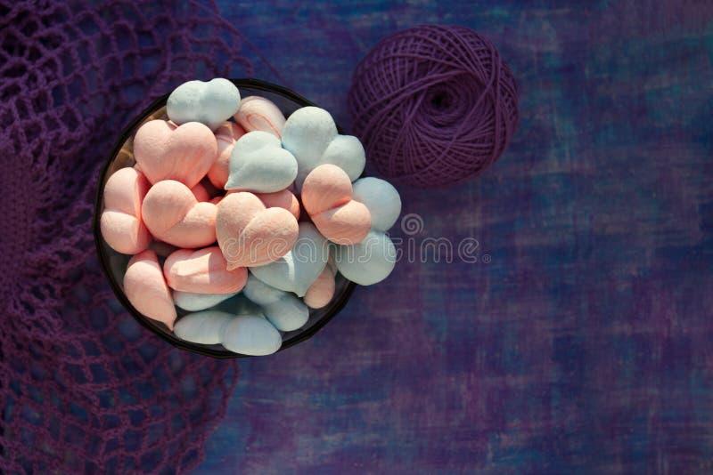 Rose et coeurs bleus de meringue sur le fond pourpre peint avec la rayure et la maille violette de coton, et boule de fil de coto images libres de droits