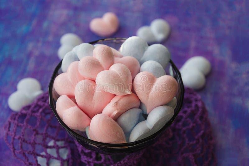 Rose et coeurs bleus de meringue sur le fond pourpre peint avec la rayure et la maille violette de coton photos stock