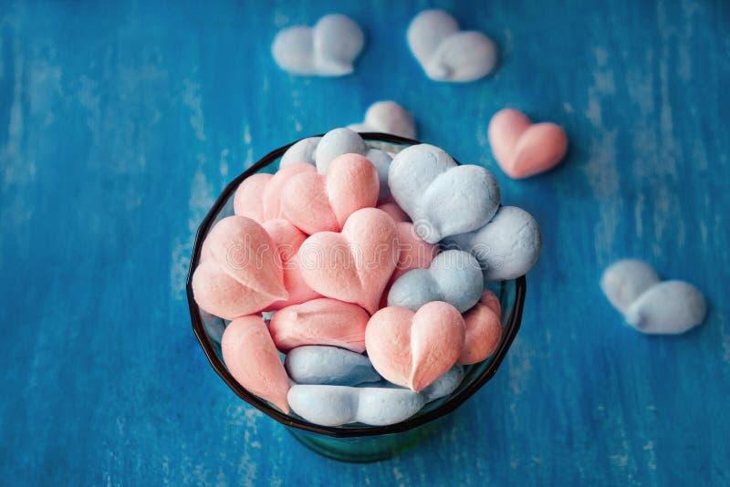 Rose et coeurs bleus de meringue sur le fond pourpre peint photographie stock libre de droits