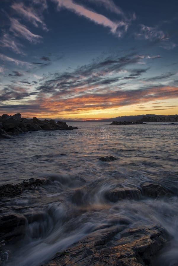 Rose et coucher du soleil orange au-dessus des roches et de la mer côtières image stock
