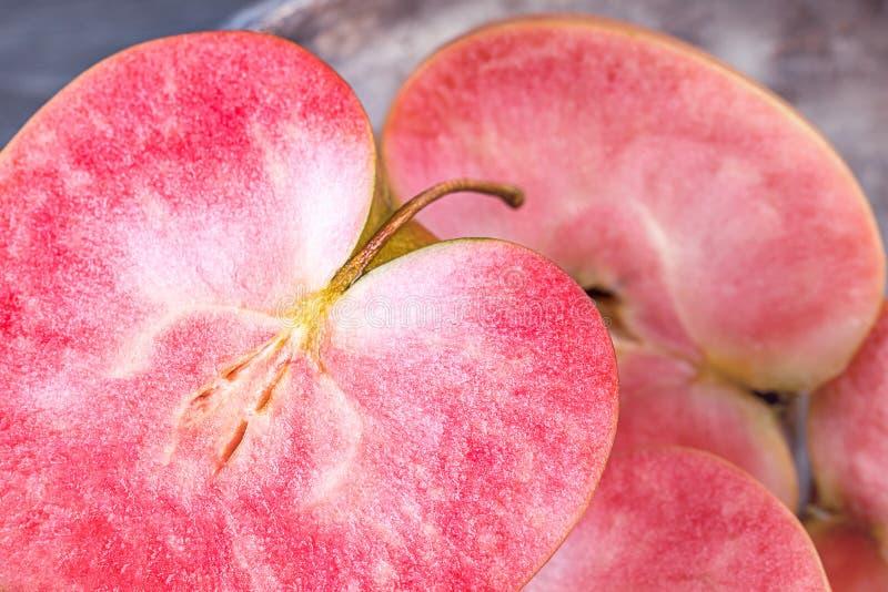 Rose et pommes étoffées rouges sur un fond foncé Pommes avec la chair rose images stock