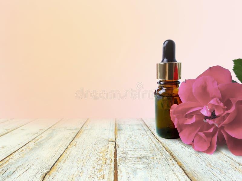 Rose, Flasche des ätherischen Öls mit leerer Tabelle auf gelbem Hintergrund lizenzfreie stockfotos
