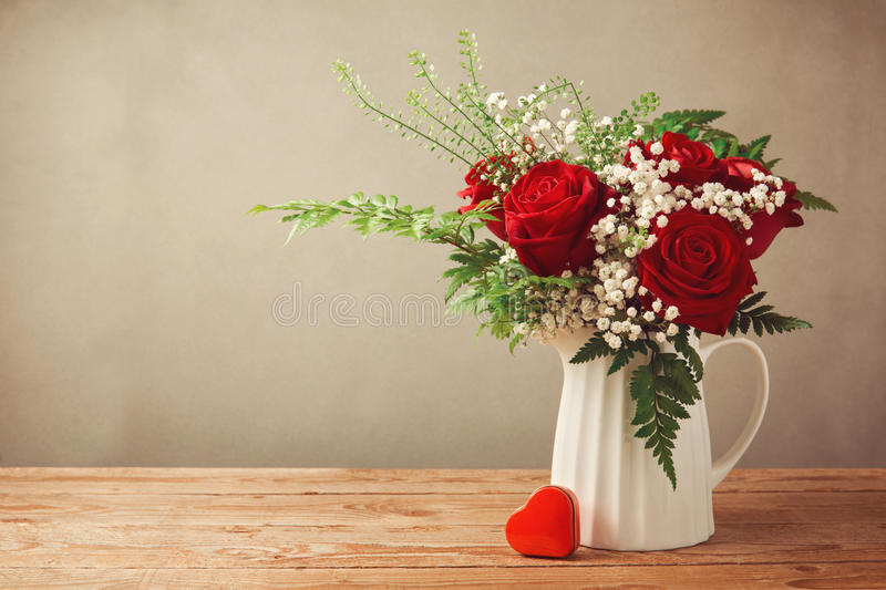 Rose flower bouquet and heart shape box on wooden table with copy space royalty free stock image