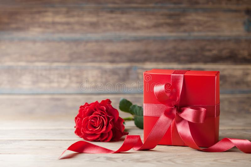 Rose flower and gift box on wooden rustic table. Mother or Valentines day greeting card. Copy space for text. Rose flower and gift box on wooden rustic table stock photo