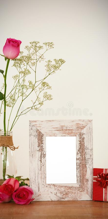 Rose flower in glass vase, photo frame and gift box royalty free stock images