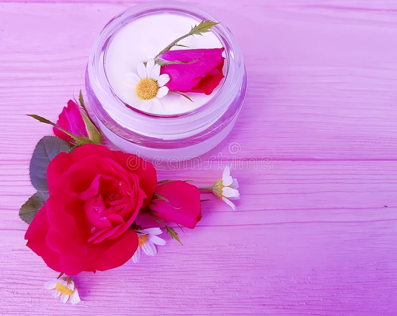 Rose flower, mask cosmetic chamomile natural, bottle cream on a pink wooden background product royalty free stock photography