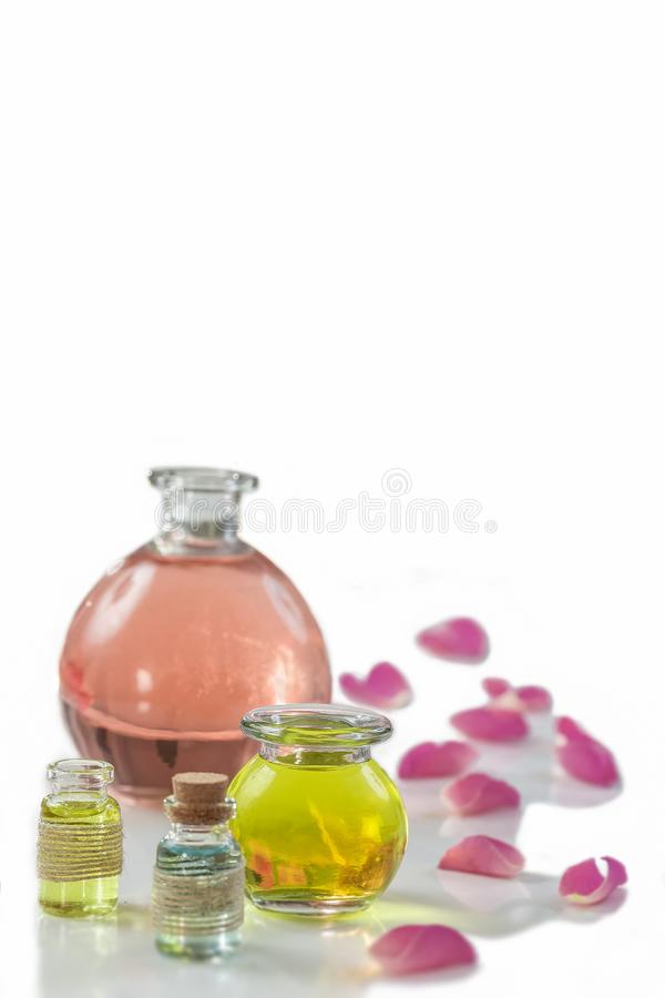 Rose flower petals with aromatherapy essential oil glass bottle over white , background, copy-space royalty free stock photos
