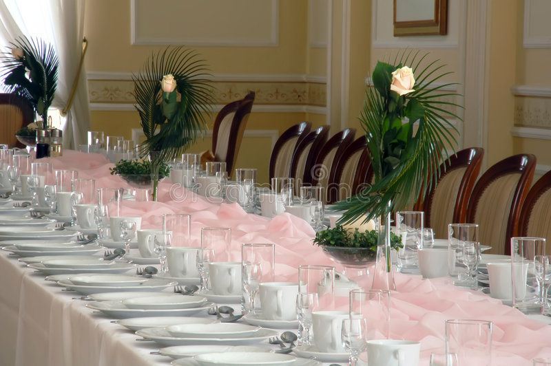 Rose flowers on banquet table. Three rose flowers on pink banquet table stock photography