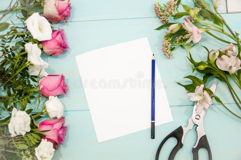 Rose flowers branch was lying on the table top to be cut with scissors, ready to make a bouquet, floral concept, preparing for the stock image