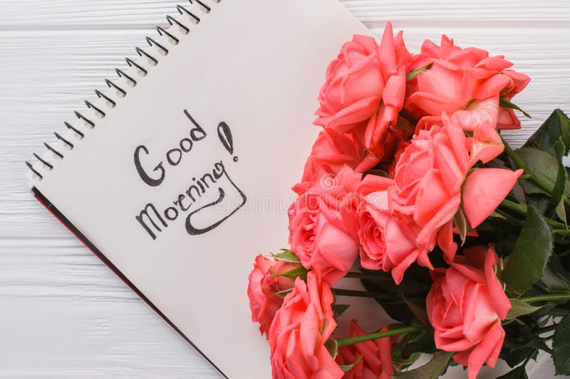 Rose flowers and good morning wish in notepad. Close up. White wooden background royalty free stock photo