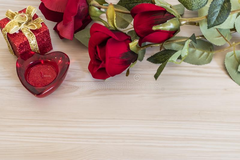Rose flowers and heart shaped candle on a wood texture background stock photography