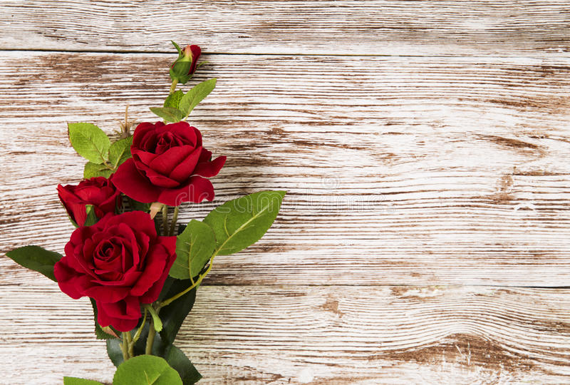 Rose flowers, red on wooden grunge background, floral card royalty free stock images