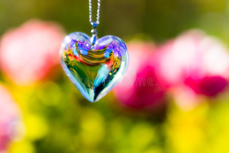 Heart crystal glass refract sunlight - rose garden background. AT 1/4/2019 in Rose garden stock photo
