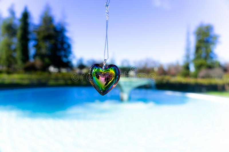 Heart crystal glass refract sunlight - fountain background. AT 1/4/2019 in Rose garden stock image
