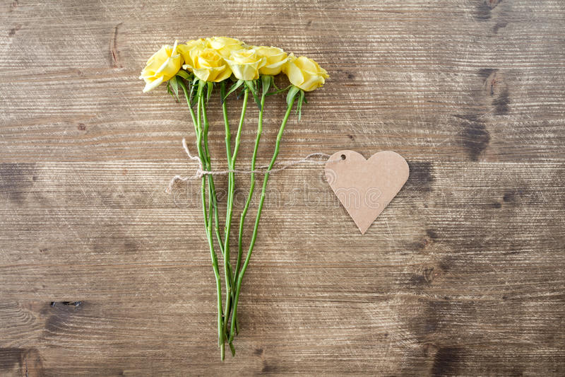 Rose gialle con l'etichetta a forma di del cuore immagine stock