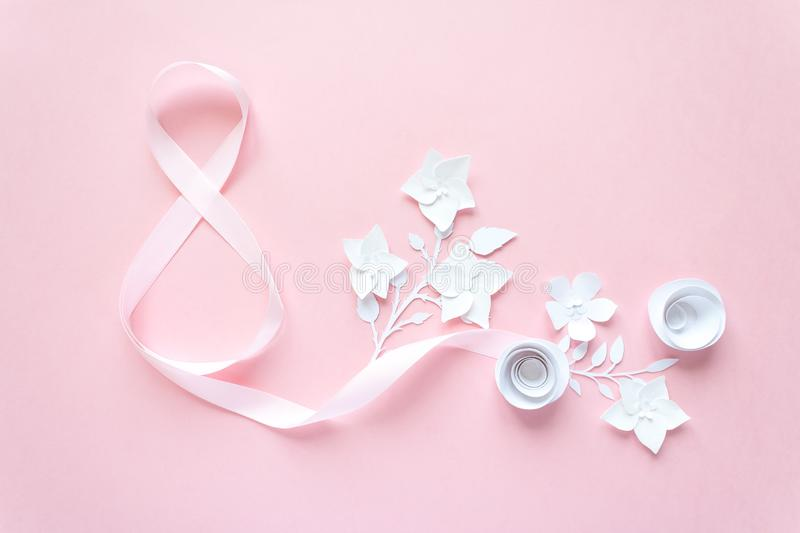 Rose gift celebration ribbon in 8 digit shape with paper flower. Over pale pink background stock image