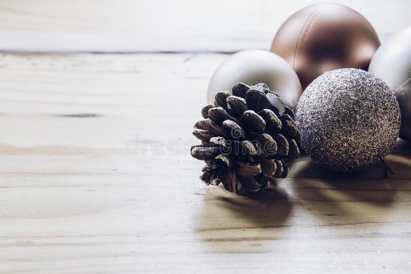 Rose gold Christmas decoration baubles and pine cone. On a wooden table stock images