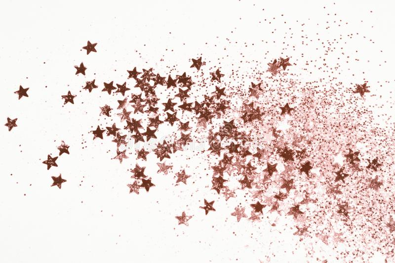 Rose gold glitter and glittering stars on light gray background. Beautiful abstract backdrop for vip design, fashion, make up, nail art, shopping, cards design stock images