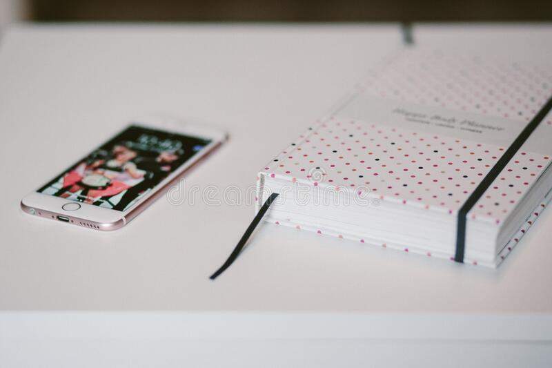 Rose Gold Iphone 6s Beside White and Black Polka Dots Book Both on Top of White Wooden Table stock photography