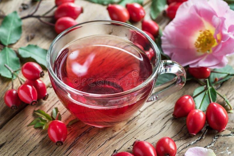 Rose-hips e óleo de sementes de rosas na mesa de madeira fotografia de stock royalty free