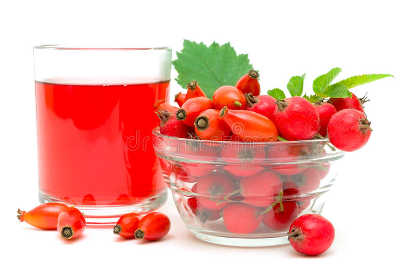 Rose hips, hawthorn and drink on a white royalty free stock images