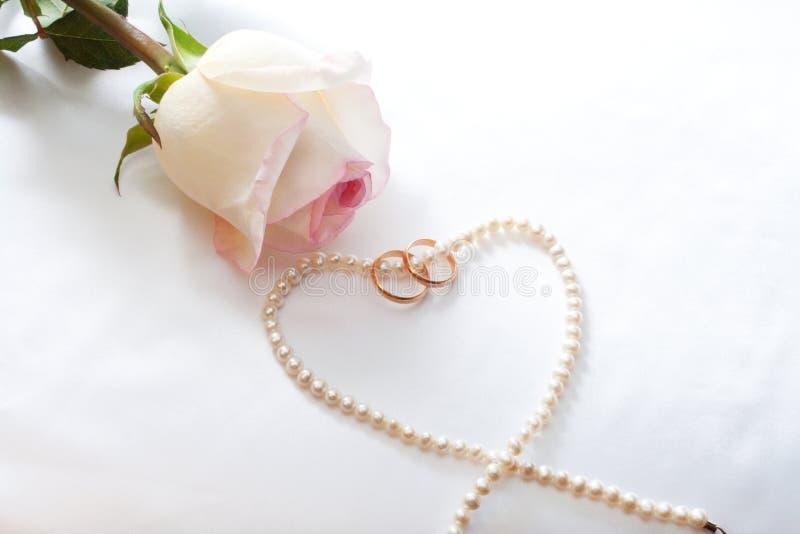 Rose, Hochzeitsringe, Perl-Halskette stockfoto