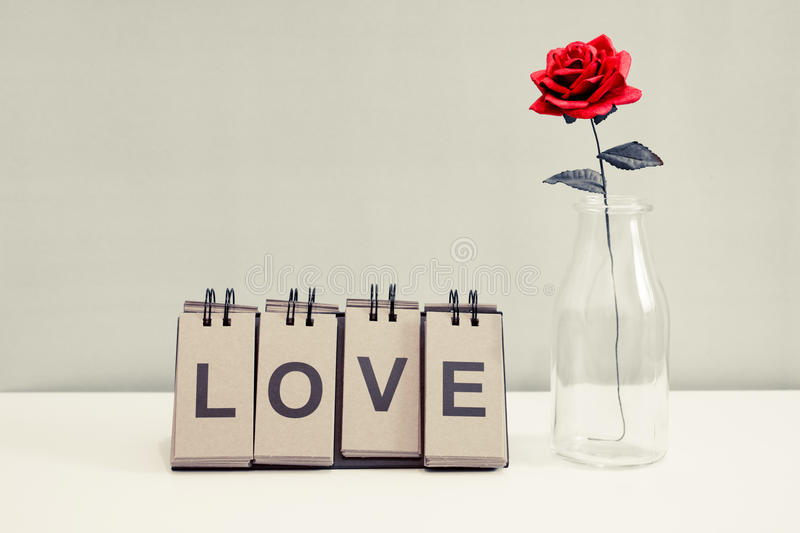 Rose and love. Rose and label LOVE placed on the desk - only red color effect stock photo