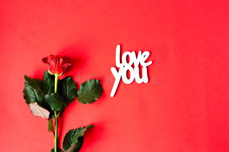 Rose mit einer hölzernen Aufschrift lieben Sie lizenzfreie stockfotografie