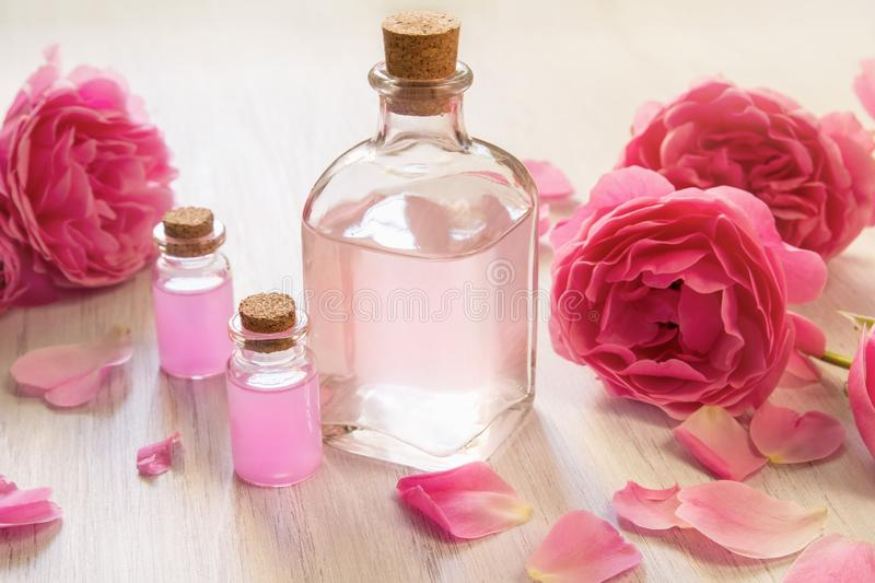 Rose oil in glass bottles with bright pink flowers on white wooden background royalty free stock image