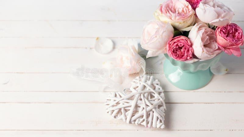 Rose pastelli nel vaso del turchese e nel cuore decorativo sul wo bianco immagine stock libera da diritti