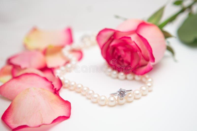 Rose, pearl and diamond ring. Rose, rose petal, pearl and diamond ring stock image