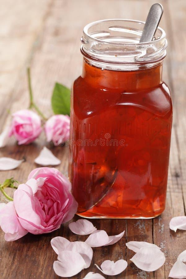 Rose petal jam. Jar of rose petal jam on a wooden table stock image
