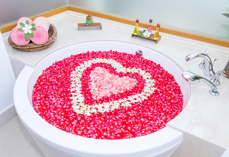 rose petals and leelawadee with heart shape decoration in bathtub and two towel, soap, shampoo, hair cream near bathtub royalty free stock photo