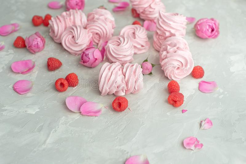 Rose and rose petals, raspberries, homemade pink marshmallows on a concrete background. stock photo