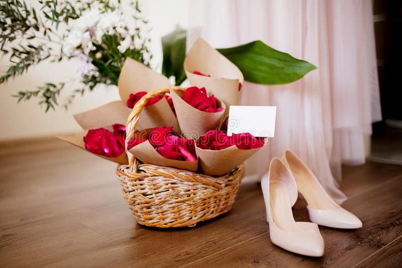 Rose petals for wedding, bride`s shoes and dress. Red rose petals for wedding in the wooden basket, bride`s shoes and dress, rustic style. Wedding preparations royalty free stock photo