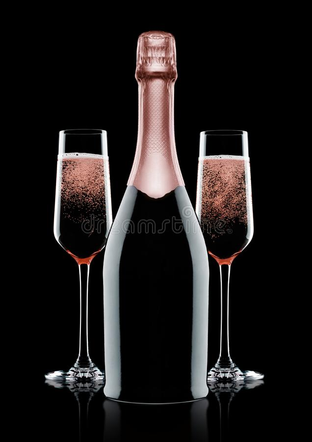 Rose pink champagne glasses and bottle on black royalty free stock image