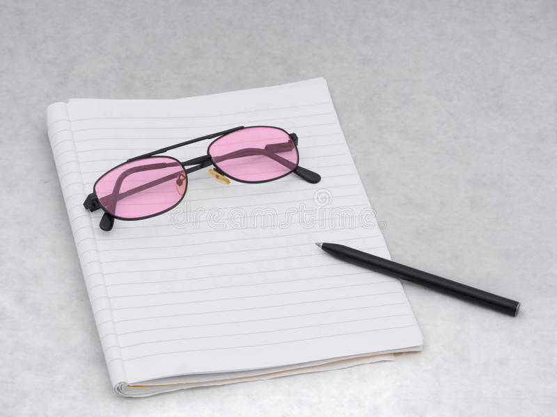 Rose pink tinted glasses with notebook and pen, for writing. Dyslexia, visual stress or optimistic outlook. Optmism or helpfu for Dyslexia, visual stress stock photo