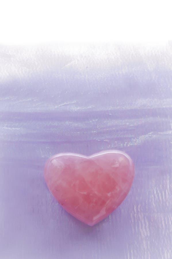 Rose Quartz Heart con el fondo de la lavanda imagenes de archivo